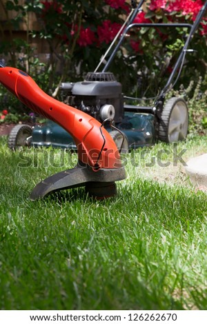Woman is trimming her lawn with electric edge trimmer. - stock photo