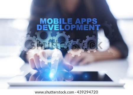 """Woman is using tablet pc, pressing on virtual screen and select """"Mobile Apps development"""".  - stock photo"""