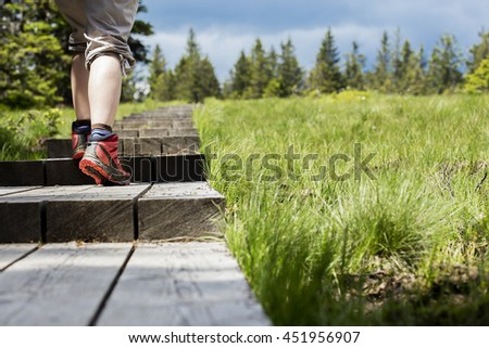 Woman is walking on a wooden path.