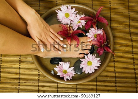 Woman is washing her feet and hands in bowl of water with flowers