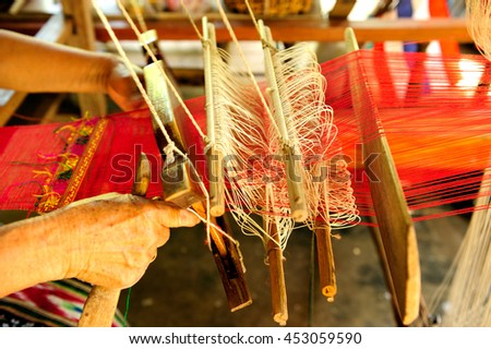 Woman is weaving textile with loom - stock photo