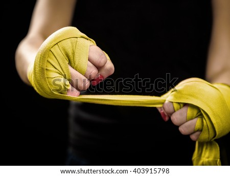 Woman is wrapping hands with yellow boxing wraps. Self Defense for Women. Isolated on black with red nails. Strong hand and fist, ready for fight and active exercise - stock photo