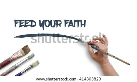 Woman is writing FEED YOUR FAITH with paintbrush.
