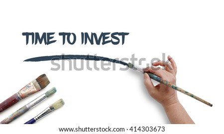 Woman is writing TIME TO INVEST with paintbrush.