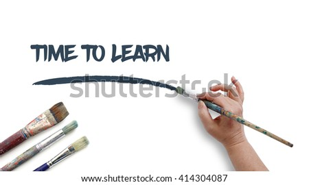 Woman is writing TIME TO LEARN with paintbrush.