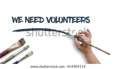 Woman is writing WE NEED VOLUNTEERS with paintbrush.