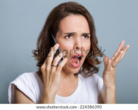 Woman is yelling at phone - stock photo