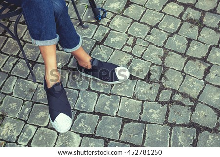 Woman jeans and sneaker shoes sitting on outdoor relax lonely and alone with brick wall road - stock photo