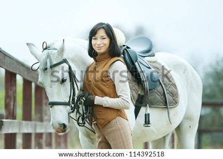 Woman jockey is walking by the horse outdoor - stock photo