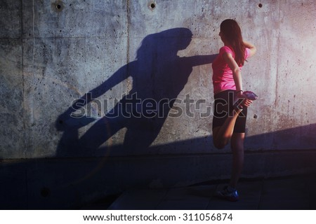 Woman jogger in bright sportswear resting after run, portrait of female jogger stretching her legs against concrete wall background with copy space area for your text message or advertising content - stock photo