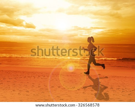 Woman jogging alone at beautiful sunset in the beach, summer sport and freedom concept - stock photo