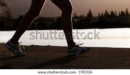 Woman jogging along a river at sunset - stock photo