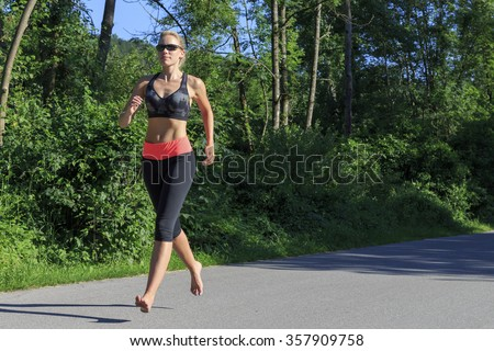 Woman jogging barefoot - stock photo