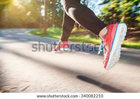 Woman jogging down an outdoor trail at sunset - stock photo
