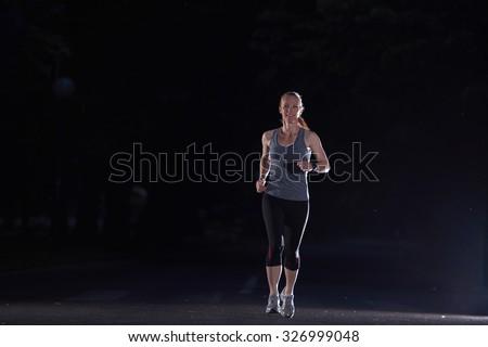 woman jogging in night dark, early morning running training - stock photo
