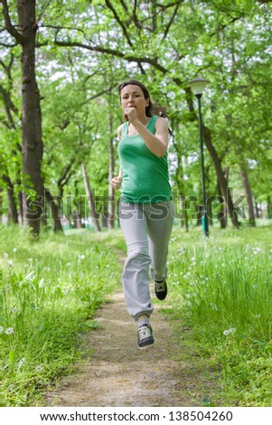 Woman jogging in the park at beautiful spring day - stock photo