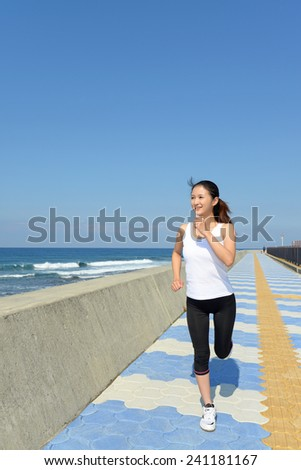 Woman jogging on beach side