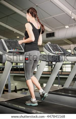 Woman jogging on treadmill at gym