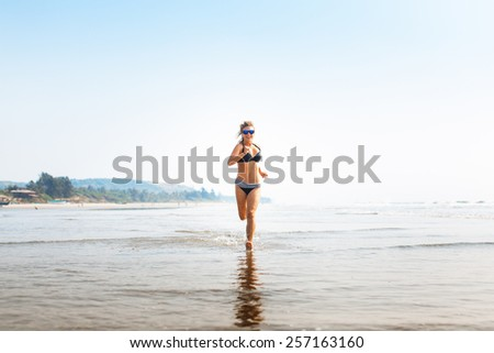 Woman jogging on wide sandy beach at bright sunshine - stock photo