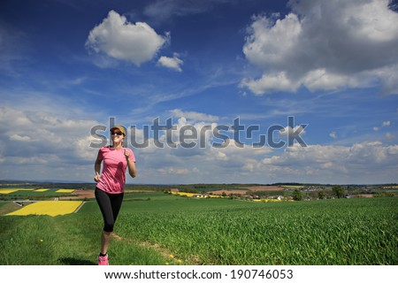 woman jogging through fields at the springtime