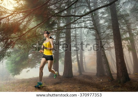 Woman jogging. Young girl running in the woods. Runner athlete in the forest.