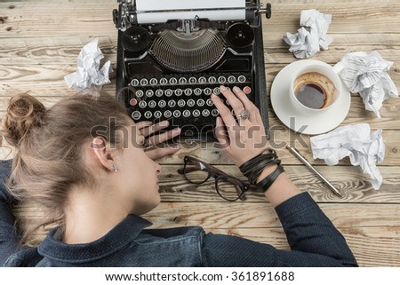 Woman journalist writer wearily folded her head next to the typewriter. Deadline storyteller. Abraham tedious work time trouble - stock photo