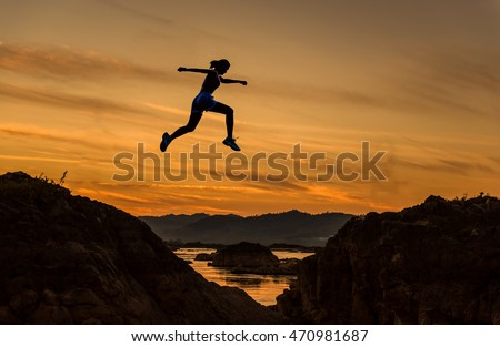 Woman jump through the gap between hill.man jumping over cliff on sunset background,Business concept idea