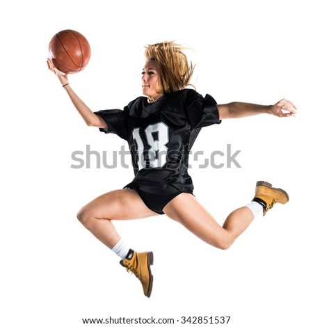 Woman jumping and playing basketball