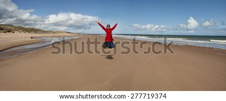 Woman jumping for joy by the beach