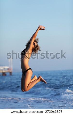 Woman jumping in bikini, on sea water. Relax, vacation - stock photo