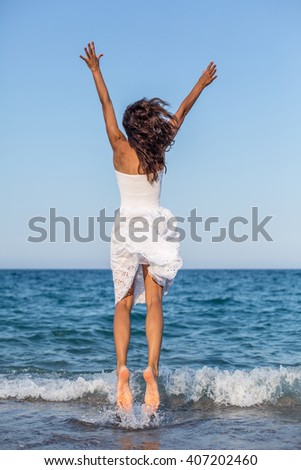 Woman jumping in the sea water. - stock photo