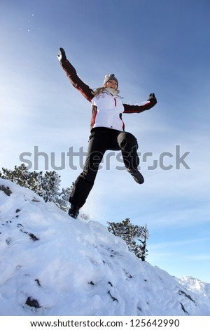Woman jumping in the snow - stock photo