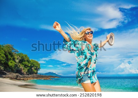 woman jumping on a beach holding a hat - stock photo