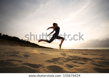 Woman jumping on beach - stock photo