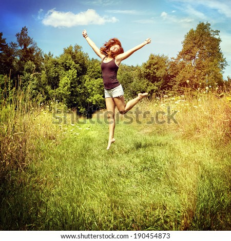 Woman jumping on nature walkway, instagram filter style