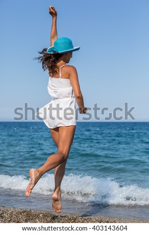Woman jumping on the beach near the edge of water. - stock photo