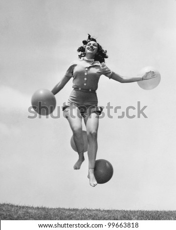 Woman jumping outside with balloons - stock photo