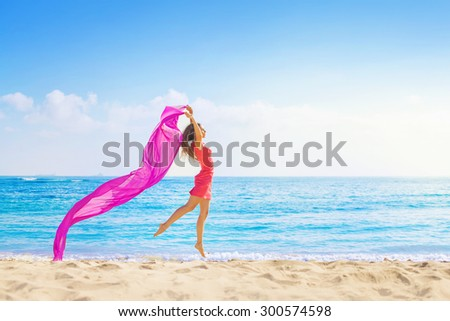 Woman jumping with cloth on a beach - stock photo