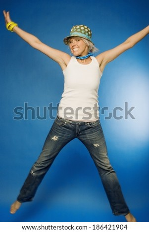 Woman Jumping With Her Arms Outstretched - stock photo