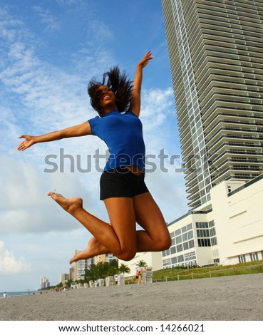Woman Jumping With Legs Bent Back - stock photo
