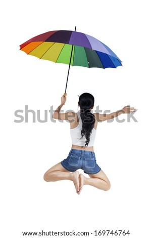 Woman jumping with rainbow umbrella isolated on white background - stock photo