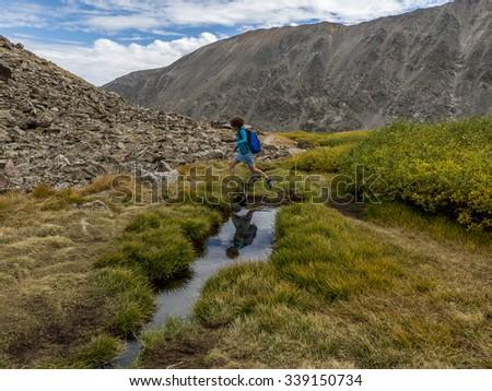Woman jumps across creek along the Blue Lakes Monte Cristo Gulch trail, Rocky Mountains near Breckenridge, Colorado - stock photo