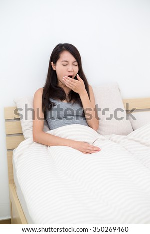 Woman just wake up and yawning on bed - stock photo
