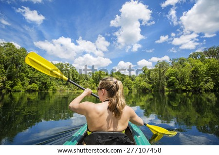 Woman kayaking along a beautiful tropical jungle river. Lots of copy space above and view from behind - stock photo