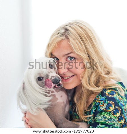 Woman keeping Chinese crested dog near her face