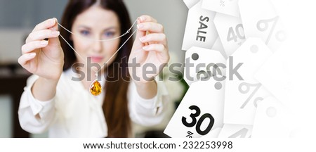 Woman keeping necklace with yellow sapphire at jeweler's shop, seasonal sale. Concept of wealth and luxurious life - stock photo