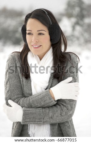 Woman keeping warm outside in the snow