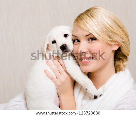 Woman keeping white labrador puppy near her face