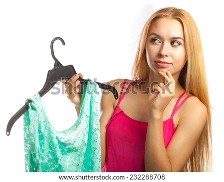 Woman keeps blouse and can't choose to buy or not - stock photo