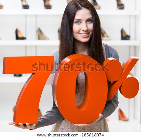 Woman keeps the model of 70% sale on footwear standing at the shopping center against the showcase with pumps - stock photo